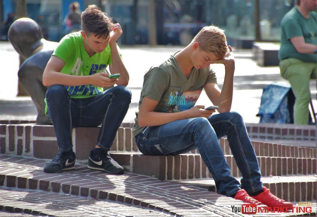 ngồi nhìn vào điện thoại của các cậu bé tuổi teen
